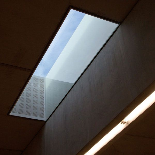 The reading room is open plan, lit from above by means of staggered roof lights with glass vertical planes on the north face bouncing and reflecting the southern light