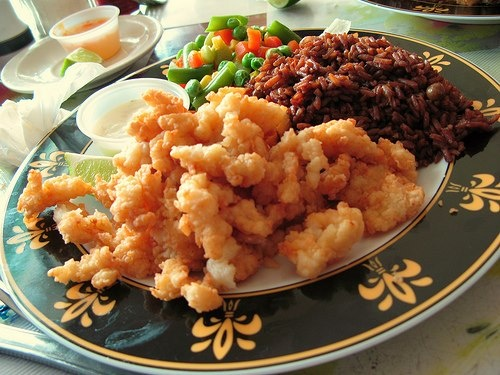 Cracked Conch, dinner served with peas and rice, mixed vegetables and tartar sauce