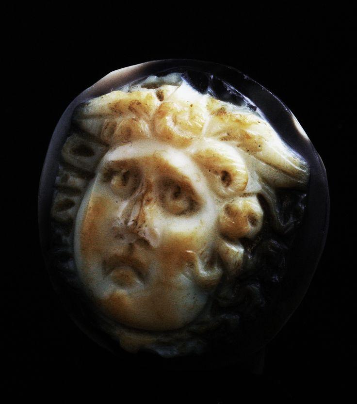 Camée circulaire en onyx, figure blanche sur fond sombre, gravé en haut-relief d'une tête de Méduse vue de trois-quarts. Ce type de talisman était appelé « gorgonéion ».Visage expressif, coiffure ailée, mèches évoquant latérales les serpents, du type « beau et pathétique » dit « Medusa Rondanini ».Le sujet de la gorgone Méduse, dont la tête tranchée fut offerte par Persée à Athéna qui en orna le plastron de sa cuirasse pour pétrifier ses ennemis, fut très utilisé durant l'Antiquité romaine…