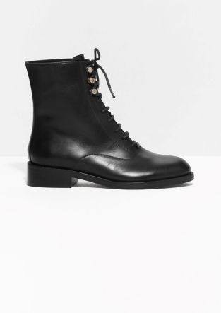 Sleek leather and gilded detailing fuse polish with an industrial edge in these impactful lace-up boots featuring a low block heel for everyday comfort.
