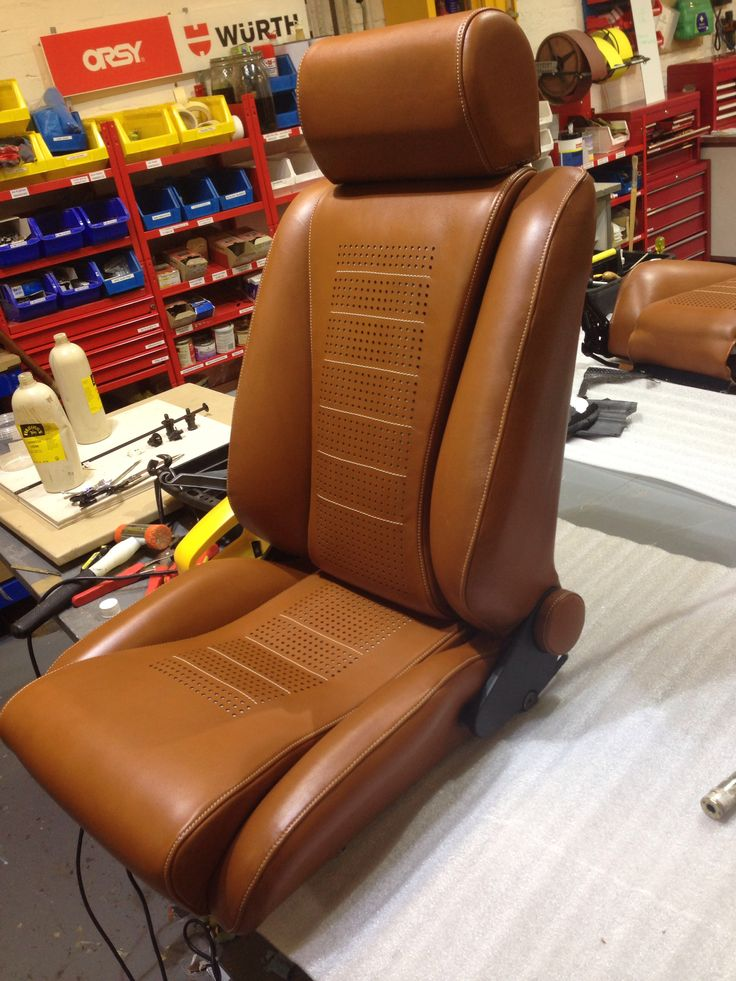 Tan leather seat, laser cut perforated seat pads inspired by driving gloves.