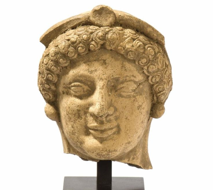 Greek archaic terracotta kore head, Hipponion, Vibo Valentia, 5th century B.C. Greek archaic terracotta kore head, Hipponion, Vibo Valentia. Almond shaped eyes, greek smile, curly hair surmounted by diadem,  round earrings, 10,5 cm high. Private collection, ex Virzi collection