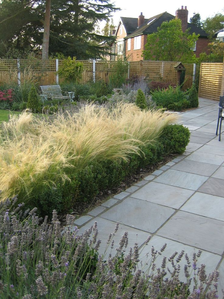 Large patio area paved in shades of grey - Silver Birch sandstone with matching setts edging from part of a country garden design by Sue Davis of outside-rooms.co.uk