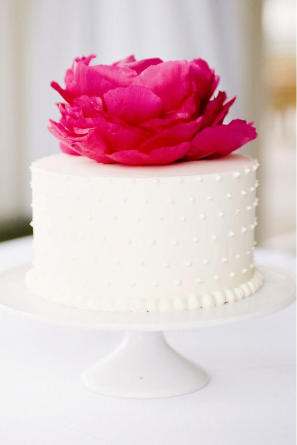 I love everything about this cake, the simple white cake, the buttercream dots, the huge pink flower. Sigh.