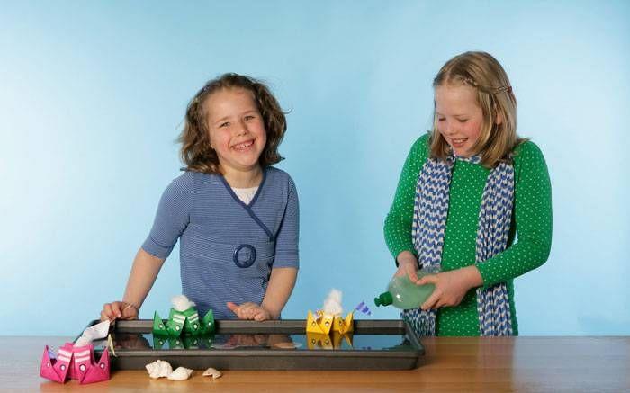Experimente für Kinder: Die Zugabe von Spülmittel im Wasser verändert die Oberflächenspannung. In diesem Versuch lassen Sie mit Ihrem Kind kleine Schiffchen fahren und sinken. Um das Experiment durchzuführen, basteln Sie zuerst schöne bunte Boote aus Papier.