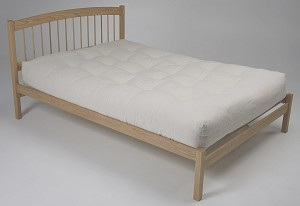 Swing Platform Bed. Designed in New Mexico this bed features a curved headboard with wooden dowels and a low footboard design. Made in the USA.