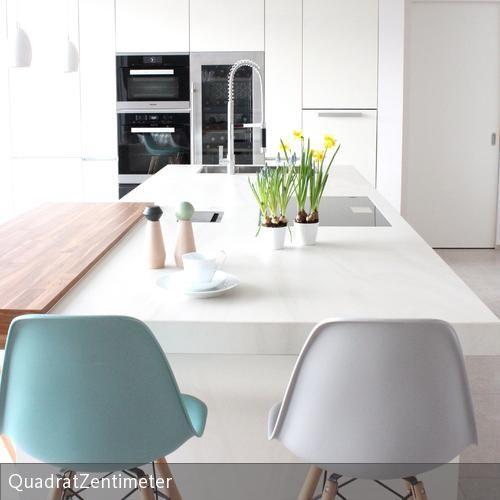 Das helle Farbkonzept des offenen Bereiches Kochen-Essen-Wohnen wird durch kleine Farbakzente aufgelockert. #küche #einrichten #eames