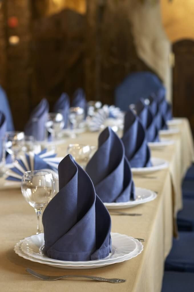 A beautiful, simple arrangement of white scalloped edge dishes paired with elegantly folded navy napkins