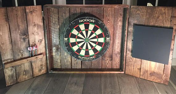 Beautiful rustic looking hand made dartboard cabinet! Nice metal hinges on doors and 2 latches on front when not in use. Beautifully stained and ready to go. Holds 6 darts on cabinet door and comes with chalkboard. Dartboard and darts not included.