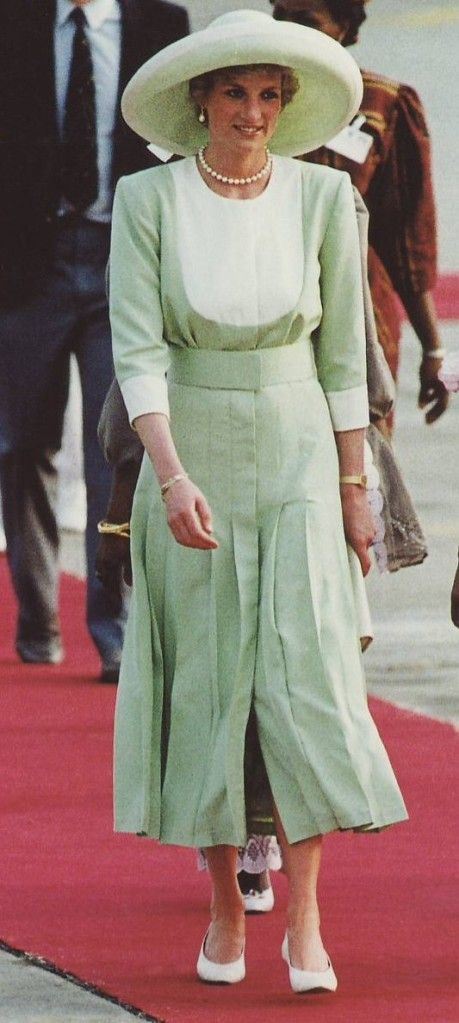 Diana, Princess of Wales during an official visit to Nigeria, in 1990. She's wearing a single strand of pearls and pearl drop earrings. Diana's celadon green suit is by Catherine Walker and her hat is by Philip Somerville.