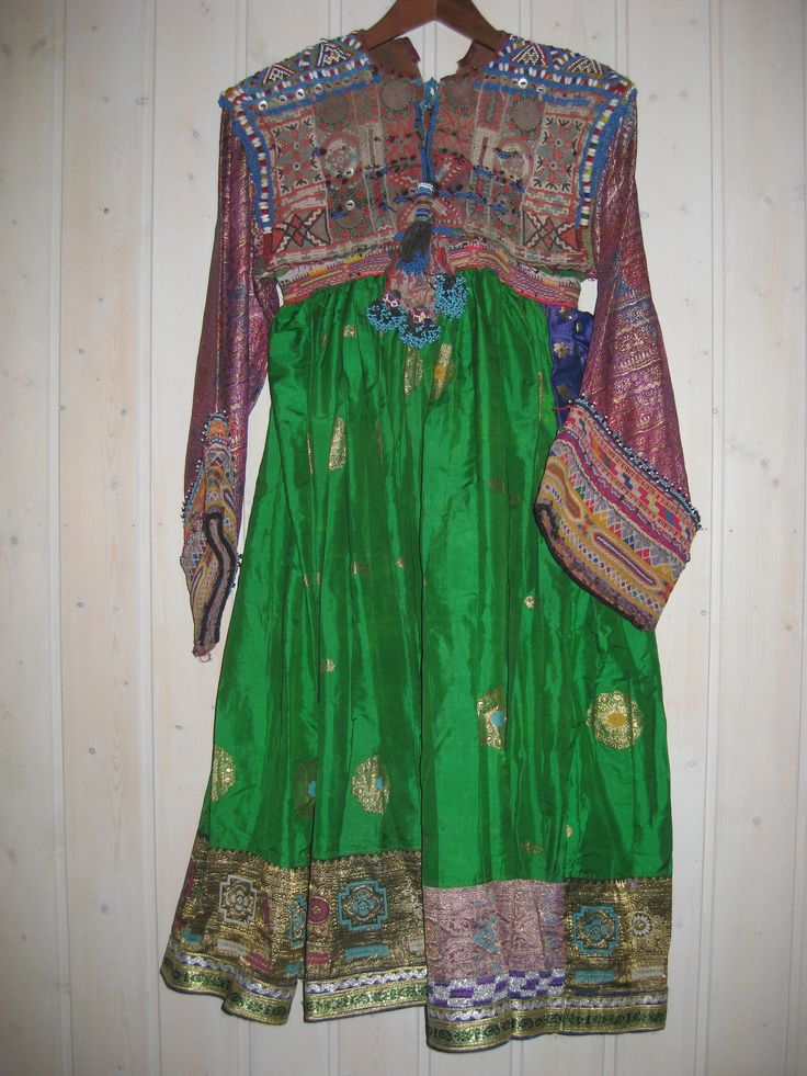 Woman's dress. The Kochi are nomadic herders and gypsies and their clothing is particularly flamboyant. Their dresses, brought back to the West, are those that identified Afghanistan in the 1970s hippie era. This dress is of green silk with sari border. The bodice is heavily covered with coins and beadwork, including jul-i-peron discs; while these have an ancient history, the silver cording on the hem is modern.