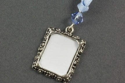 Photo Frame Wedding Charm The Photo Frame Wedding Charm is a pretty way to remember a loved one at your wedding by placing their photo into the frame and attaching it to your bouquet. The charm is embellished with a swarovski crystal bicone bead and satin ribbon. Each charm is presented in a pretty organza drawstring bag. Available in gold or silver and a fabulous range of bead and ribbon colours.