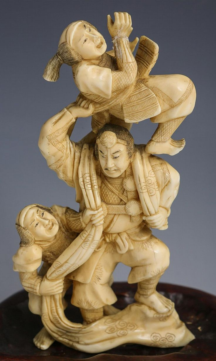 """JAPANESE CARVED IVORY OKIMONO FIGHTING SAMURAI Japanese carved ivory okimono, late 19th/early 20th C., Samurai fighting two smaller warriors. Signed on underside. Includes wood base. Provenance: Private Minnesota estate. Weight: 203g without base Size: 6"""" without base"""