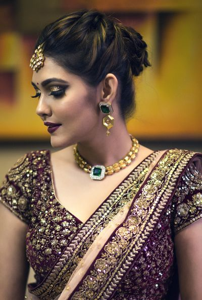 Bridal Makeup and Hair - Bride Wearing a Gold Choker with a Green Emerald and Bronze Makeup | WedMeGood  #wedmegood #makeupandhair #weddingmakeup #weddinghair #hairbun