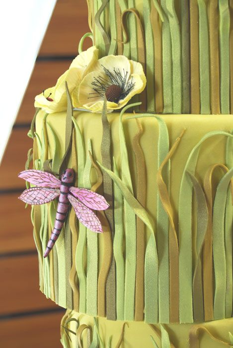 Naturally - Rachel and Bret's reception was held at the fabulous McNamara Center in Minneapolis. Part of the appeal to them, was the architect's replication of the landscape of Minnesota in the design of the building. To follow suit, we designed a cake completely covered in fondant lake grass.  Add in some frosting flora and fauna and even a pair of frosting bumblebees donning a tophat and veil, and we had a cake that suited the couple perfectly.  After all, this bride could rock a Moniqu