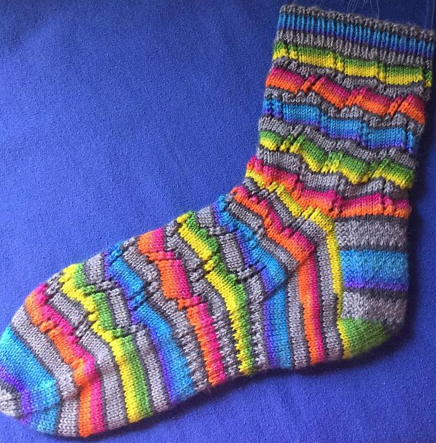 Tumbling Blocks Socks pattern plays with self-striping, fingering weight yarn and the end result is a sock with some pizazz! The easy-to-knit lace columns combined with stripes give the effect of blocks that are tumbling.