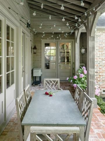 French Country covered patio... I love the great lights, the long, luscious table in that luscious color, the white bank of windows and french doors, the wood work, and the used brick. Very nice.... very well done. I wonder how close it is to the kitchen.