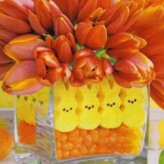 Orange jelly beans, yellow peeps, and orange tulips arranged in layers making an adorable Easter centerpiece.