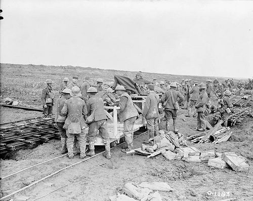 German prisoners and Canadian Red Cross men assist in the dispatching of wounded on a light railway. Vimy Ridge. April, 1917.