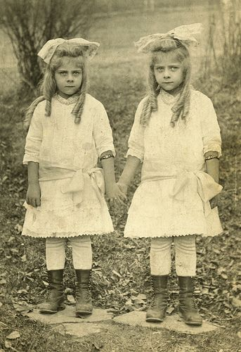 Identical Twin Girls in Bows. I guess leggings and boots are not a new trend!