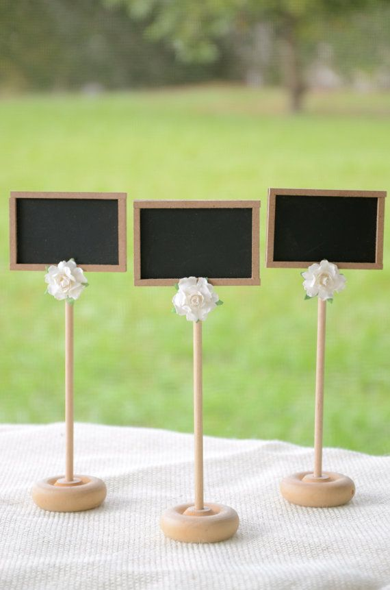 Easy DIY: small dowels and wooden bases, wood scraps, chalkboard paint, fake flowers to decorate.