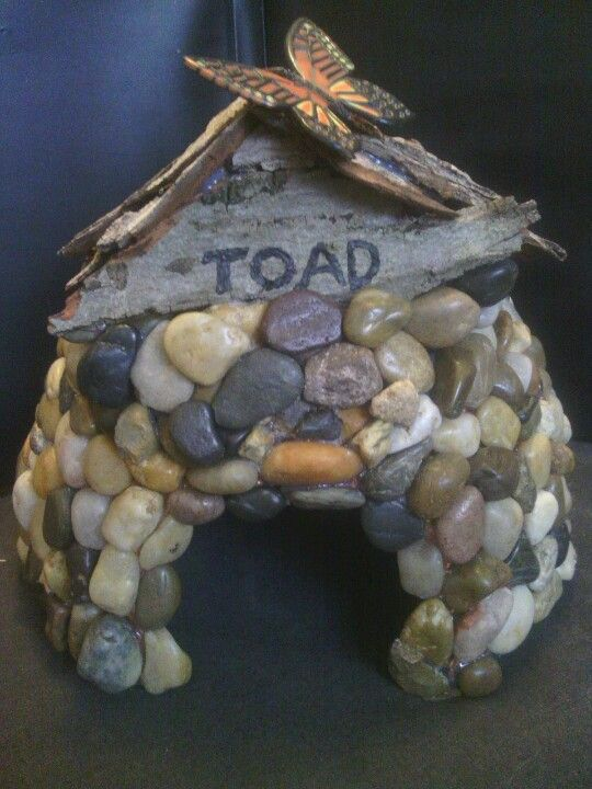 A DIY toad house made with a thrift-store terracotta pot turned upside down and Dollar Tree pebbles hot-glued on.  The roof is made from a fallen piece of old tree bark found alongside the road.  I put soil and live moss from my yard under the roof.  Hopefully the moss will eventually grow in between the pebbles to complete the look.