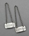 """A pair of Georgian silver wine labels, engraved """"Madeira"""" and """"Teneriffe"""". They are rectangular in shape, with a reeded border, and are complete with their original chains. Both are fully hallmarked, with makers mark DH for Daniel Hockly, duty mark, lion passant and date letter P for 1810. Daniel Hockly is an interesting silversmith, he started his career in London, entering a mark as a smallworker in 1810, it seems he specialised in wine labels. In 1819 he boarded a ship with his family and…"""