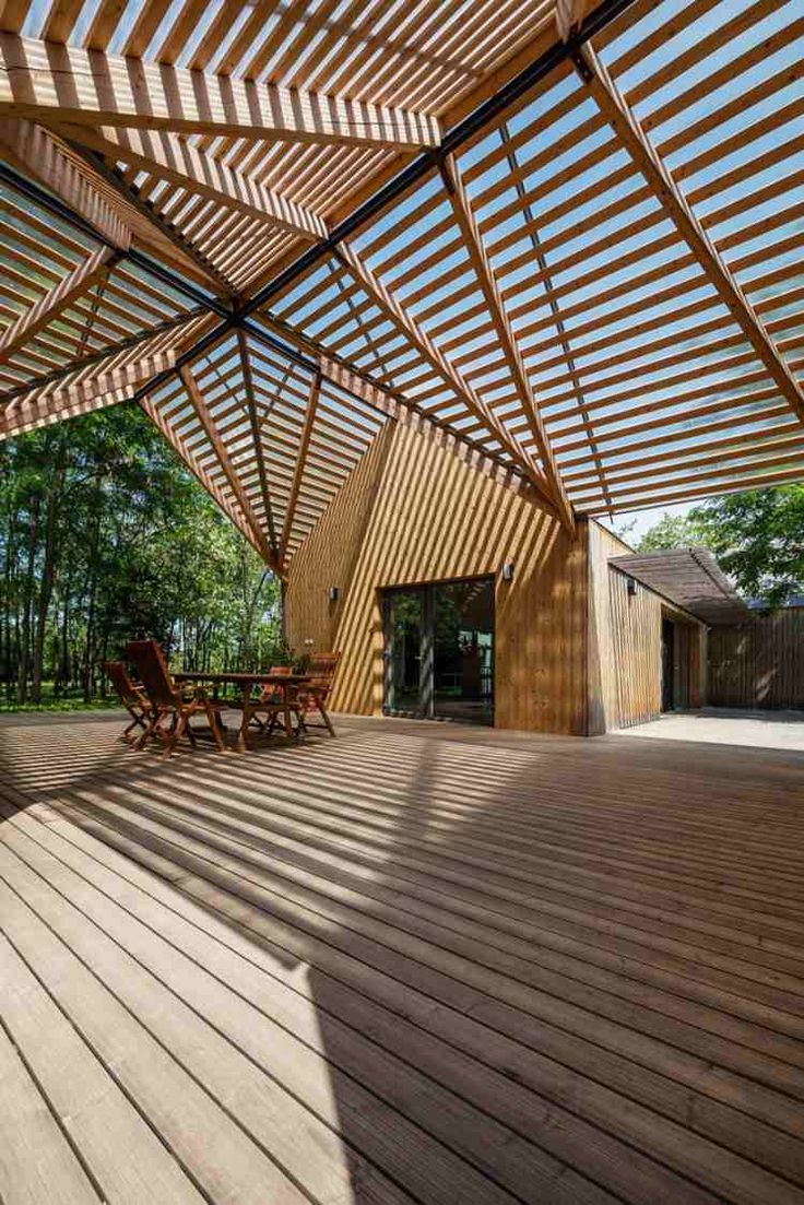 Terrasse bois spacieuse dont le toit crée un jeu de lumière et d'ombre