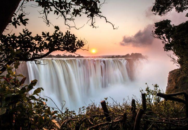 """Cataratas Victoria (Zâmbia e Zimbábue): Na fronteira entre Zimbábue e Zâmbia, na porção sul da África, as Cataratas Victoria são uma enorme força da natureza. O estrondoso som das águas caindo pode ser ouvido a até 40km de distância. Não é à toa que os locais a chamavam de """"Mosi-o-Tunya"""": a fumaça que troveja. Descoberta pelo explorador e missionário David Livingstone em 1855, a cachoeira ganhou o atual nome em homenagem à rainha Vitória. É considerada uma das Sete Maravilhas Naturais do…"""