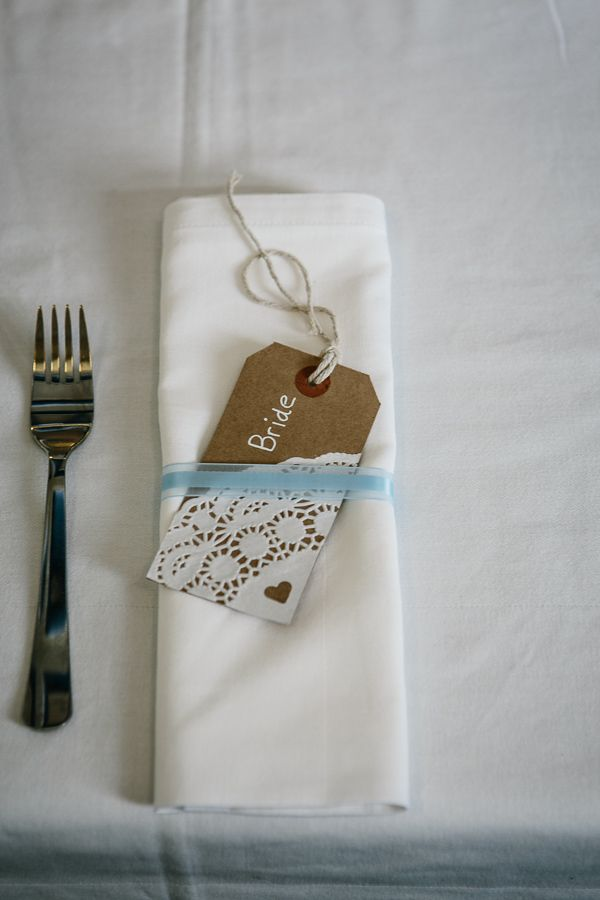 Homemade name places with brown luggage tags and paper doilies.