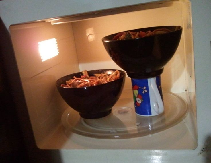 Use a microwaveable cup to heighten a bowl to create space for two items to be heated up