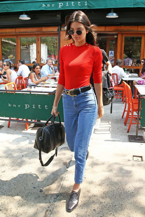 Kendall Jenner in a red sweater, high waisted skinnies, and a western style belt