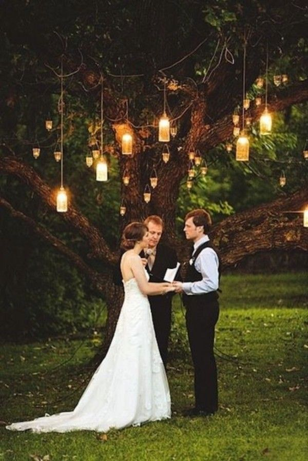 Candlelit mason jars hanging from a tree are simple yet beautiful and perfect for a twilight ceremony in the country.