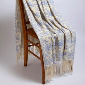 """Whether draped across your bed or favorite arm chair, this indulgent cashmere-wool throw adds warm elegance with a floral motif and fringed trim.    Product: ThrowConstruction Material: Cashmere and woolColor: Crème fraiche and blueDimensions: 50"""" x 65"""" Cleaning and Care: Dry clean"""