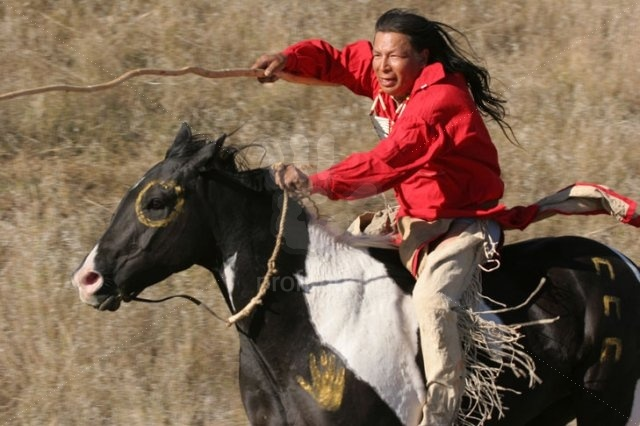 A Native American Indian (Sioux) man riding horseback on a Indian horse with a coup stick in the Plain