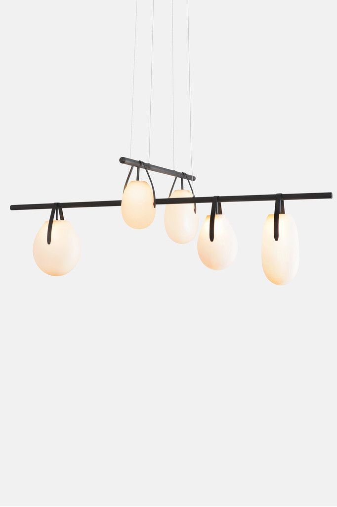 Gala is a minimal, near-weightless take on the chandelier, rethought as a simple beam with power cords hidden inside the slim suspension cables. Its ivory-frosted glass fixtures, fixed in a variety of