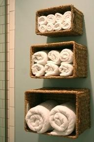 Tres canastos de diferente tamaño, invertidos y puestos como repisas en el baño
