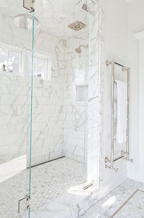 Exquisite master shower is clad in white marble subway tiles fitted with small side by side windows facing a rain shower head mounted to the marble diamond pattern tiled ceiling over a marble hex shower floor.