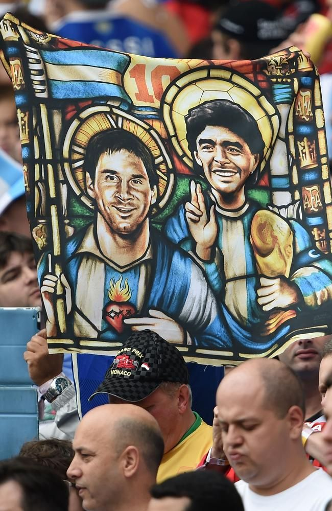 An Argentina fan holds an image of Argentina's forward Lionel Messi and former footballer Diego Maradona as Saint.