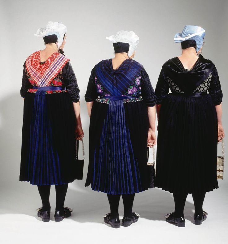 Drie dames in de dracht van Rouveen die zij nog dagelijks dragen. Zij zijn gekleed in de zondagse kerkdracht in verschillende rouwgraden: links uit de rouw, in het midden de lichte rouw en rechts de zware rouw. Voor een familielid in de eerste graad gaat men drie tot vier jaar in de zware rouw, vervolgens twee maanden in de lichte rouw, om dan weer uit de rouw te gaan. 1993 #Overijssel #Staphorst