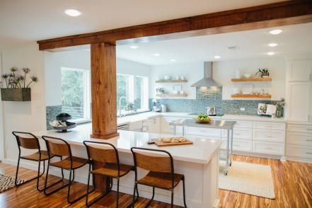 Wood-wrapped support beams provide a welcome contrast with the kitchen's white cabinets and light granite countertops
