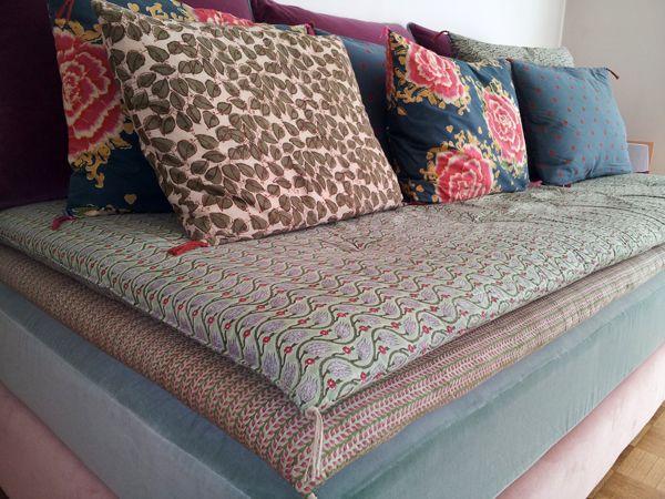 Comment transformer un lit d'une personne en jolie banquette dans un salon? Ici nous avons choisi deux velours dans des tons poudrés pour la base , dans des tissus indonésiens matelas surpiqués et coussins de décorations ont été façonnés. D'épais coussins...