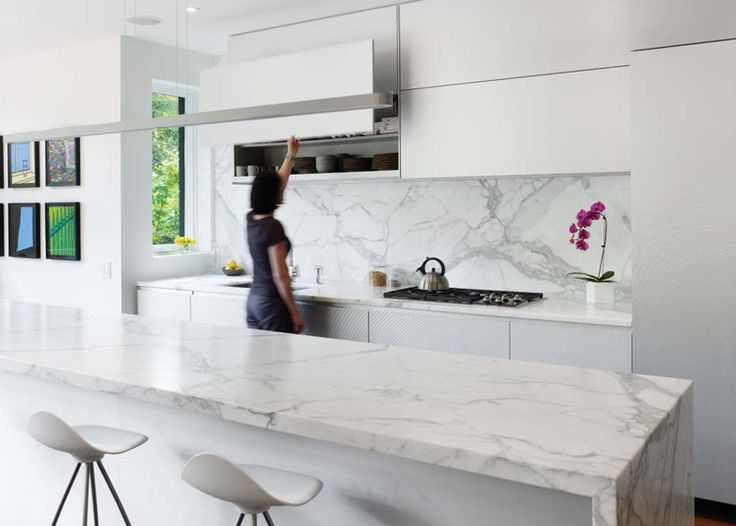 In this kitchen, a statuario marble island and backsplash provide a richness to the sleek aluminum cabinets.