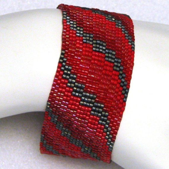 Red Bargello Ribbon Peyote Cuff (2190). This cuff is based on a simple ribbon pattern for bargello needlework. I use Japanese delica beads in matte metallic grey and three different shades and finishes of red to create this piece with one-, two-, three-, and four-drop peyote stitches.