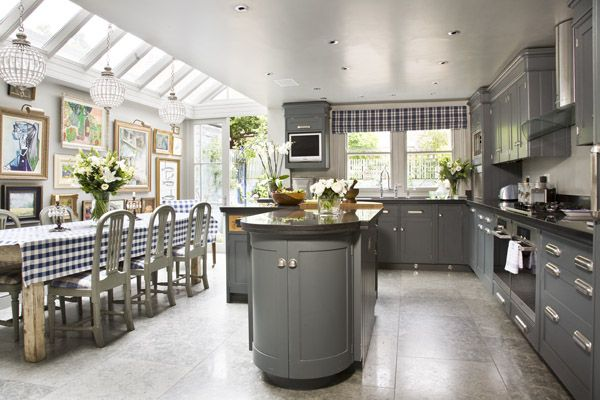 Grey painted Shaker style Kitchen. Beautifully coordinates with rustic Dining Table arrangement and wall art. Great light source from conservatory extension and chandeliers add a witty note to this rather lovely design.