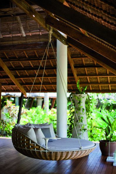Dedon Island - A hanging chair in an open-air pavilion