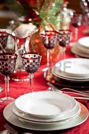 Elegant couvert met witte schotels over een rood tafelkleed plus beker en decoraties photo