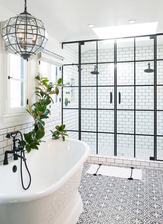 White and black bathroom boasts top half of walls painted white and bottom half of walls clad in white subway tiles finished with black grout lined with a glass faceted lantern hanging over a roll top bathtub fitted with an oil rubbed bronze tub filler placed atop a white and black Cement Tile Shop Bordeaux Tiles.