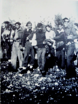 Picture of 1946, Messenia district, Greecen of the civil war era. Far-right Petropoulos militia members bring a captive civilian to execution. The man on the right of the prisoner with his hand up is Christos Petropoulos himself giving the sign to the execution of the prisoner.