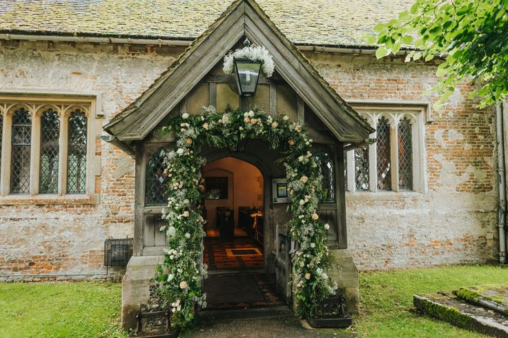 What a beautiful flower arch and 'lantern halo' by Eclectic Bliss Events at Rotherwick Church. Photo by Benjamin Stuart Photography #weddingphotography #eclecticblissevents #rotherwickchurch #ceremonydecor #churchwedding #flowerarch